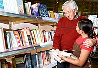 Asian grandfather and granddaughter reading in store