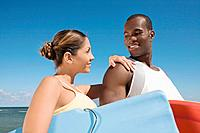 Multi_ethnic couple holding bodyboards