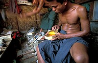 Mandalay, a man in a workshop producing the gold leaves that buddhists apply to holy shrines