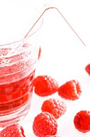 Close_up of a glass of raspberry juice and raspberries