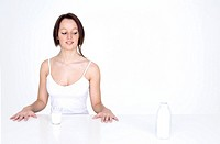 Young woman sitting at a table and looking at a milk bottle