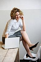 Businesswoman sitting on desk while talking on her mobile phone