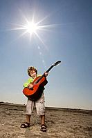 Boy playing the guitar at the beach