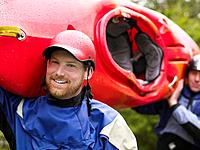 Two men carrying kayak outdoors portrait