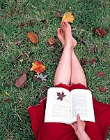 Woman sitting on grass reading book (thumbnail)