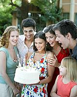 Group of people with birthday cake at a party outdoors smiling