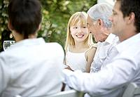 Senior man and young girl embracing and smiling at outdoor party with people around them