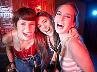 Three women in a nightclub drinking and laughing