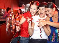 Three women with beverages in nightclub pointing and smiling