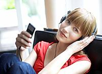Woman sitting in living room listening to MP3 player