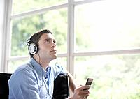 Man sitting in living room listening to MP3 player