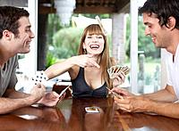 Three people playing cards at table and smiling