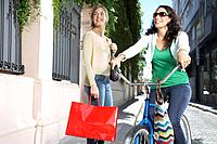 Two women outdoors with a bicycle and shopping bags smiling