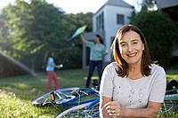 Senior woman standing outdoors near bicycles smiling
