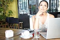 Woman in restaurant with laptop thinking and smiling