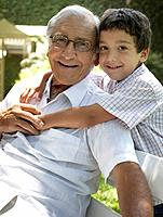 Senior man outdoors sitting on bench with young boy being affectionate toward him and smiling
