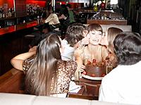 Group of people kissing and smiling at a birthday party in a restaurant