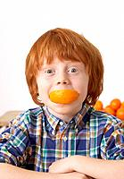 Young boy in kitchen with orange slice in his mouth