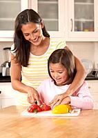 Woman and young girl in kitchen slicing bell peppers and smiling