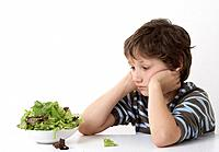 Young boy sitting by a bowl of lettuce looking unhappy