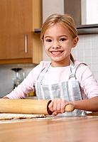Young girl in kitchen using a rolling pin on dough and smiling