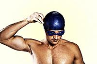 Wet swimmer with goggles on taking cap off