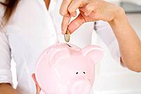 Businesswoman putting coin into piggy bank
