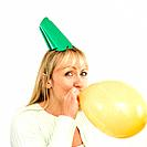Woman in party hat blowing balloon
