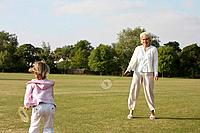 Senior woman and girl playing badminton