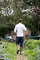Man with spading fork walking in the garden