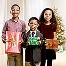 Mixed Race siblings holding Christmas gifts