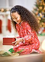 Mixed Race girl opening Christmas gift