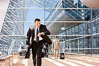 Hispanic businessman running and looking at watch