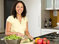 Mixed Race woman chopping vegetables