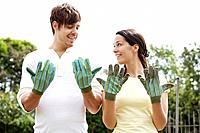 Man and woman looking at their dirty gardening gloves