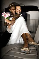 Multi_ethnic newlyweds in back of limousine