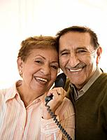 Senior Hispanic couple talking on telephone