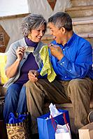 Multi_ethnic couple looking at contents of shopping bags