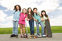 Multi_ethnic girls on roller skates, scooters and skateboards