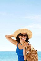 Hispanic woman wearing straw hat at beach