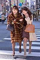 Asian mother and adult daughter crossing street