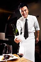 Asian waiter pouring wine