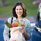 Hispanic woman holding grocery bag