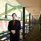Asian businessman leaning on railing