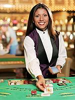 Hispanic female blackjack dealer in casino