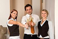 three young business people with sparkling wine glasses