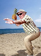 Male senior with pineapple on the beach (thumbnail)