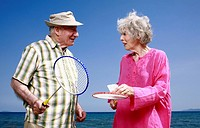 Senior couple on beach with badminton racquets and ball (thumbnail)