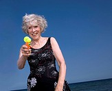 Female senior on beach with water gun