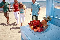 Bowl of fruit and parents with children on beach